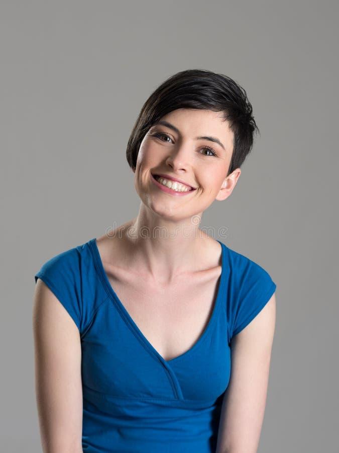 Πορτρέτο στούντιο της χαριτωμένης καλής σύντομης ομορφιάς brunette τρίχας που χαμογελά στη κάμερα με το ελαφρώς γαρμένο κεφάλι στοκ εικόνες