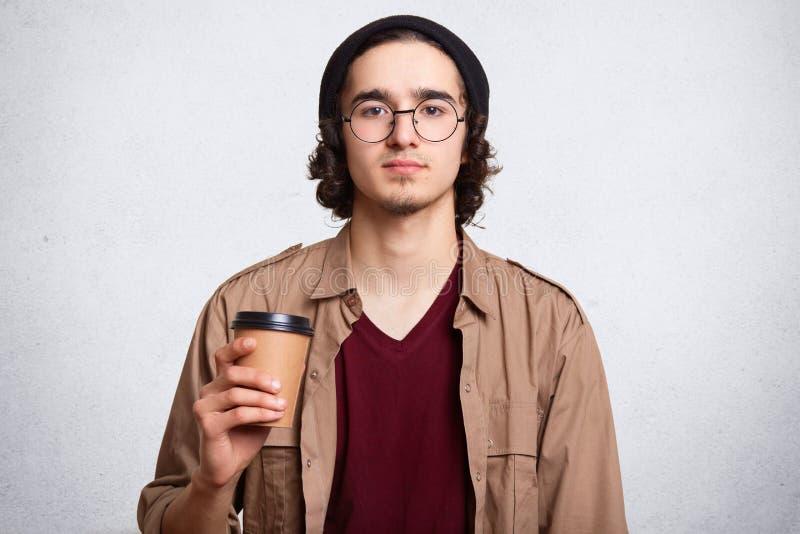 Πορτρέτο στούντιο του σοβαρού ατόμου με το φλυτζάνι του καυτού αρωματικού καφέ Τύπος που φορά τη μοντέρνη μαύρη ΚΑΠ Έννοια Hipste στοκ εικόνες