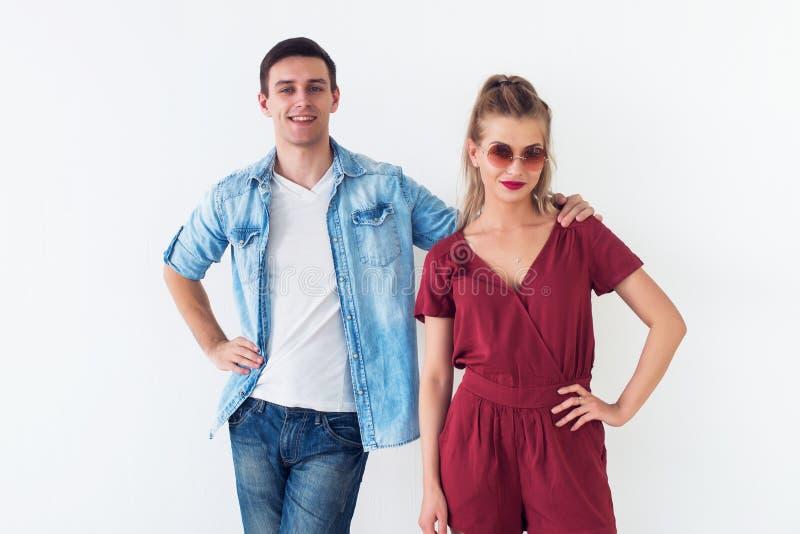 Πορτρέτο στούντιο του χαμογελώντας ξένοιαστου νέου ζεύγους που στέκεται μαζί στο άσπρο υπόβαθρο, άτομο που αγκαλιάζει κρατώντας τ στοκ εικόνες
