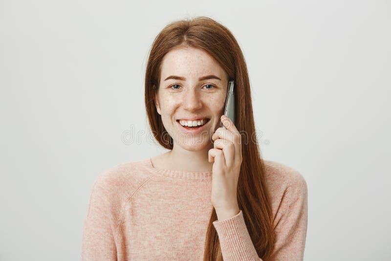 Πορτρέτο στούντιο του όμορφου καυκάσιου redhead θηλυκού προτύπου με τις φακίδες που μιλούν στο smartphone ενώ χαμογελώντας και όν στοκ εικόνες με δικαίωμα ελεύθερης χρήσης