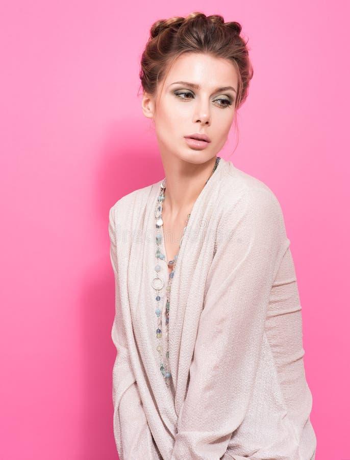 Πορτρέτο στο ρόδινο χρώμα Όμορφη νέα γυναίκα σε μια ελαφριά μπλούζα που θέτει και που κρατά τις χάντρες στοκ φωτογραφία με δικαίωμα ελεύθερης χρήσης