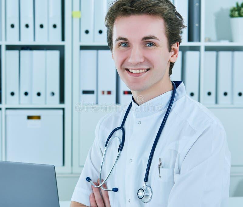 Πορτρέτο συνεδρίασης γιατρών χαμόγελου της νέας αρσενικής με τα διασχισμένα χέρια στοκ εικόνα