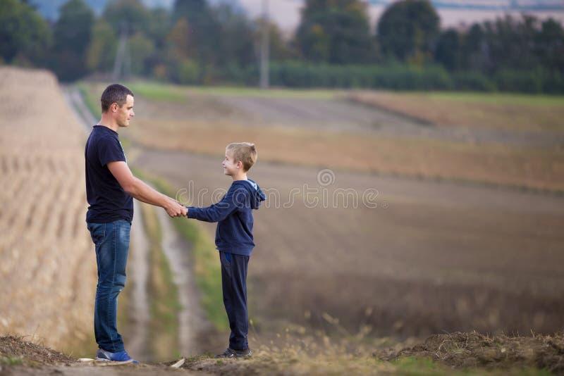 Πορτρέτο σχεδιαγράμματος του νέου πατέρα και του χαμογελώντας γιου που στέκονται στα χλοώδη χέρια εκμετάλλευσης τομέων στα θολωμέ στοκ εικόνα