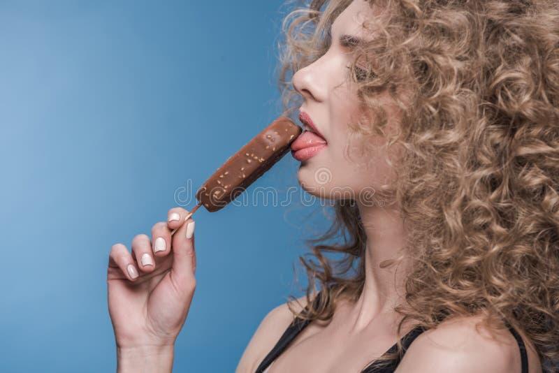 Πορτρέτο σχεδιαγράμματος της αισθησιακής ελκυστικής νέας γυναίκας που τρώει το παγωτό στοκ φωτογραφίες