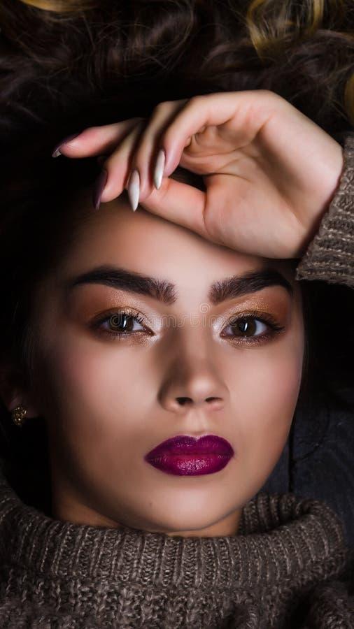 Πορτρέτο τάσης ομορφιάς μόδας του όμορφου κοριτσιού brunette με τη μακριά και λαμπρή σγουρή τρίχα Προκλητική αντιμέτωπη μωρό πρότ στοκ εικόνα