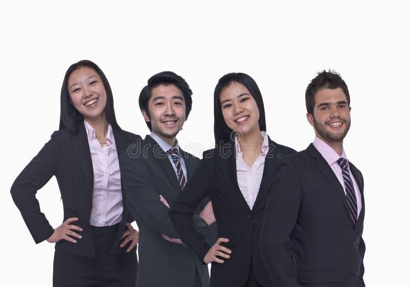 Πορτρέτο τεσσάρων νέων επιχειρηματιών που εξετάζουν τη κάμερα, τριών τετάρτων μήκος, πυροβολισμός στούντιο στοκ φωτογραφία