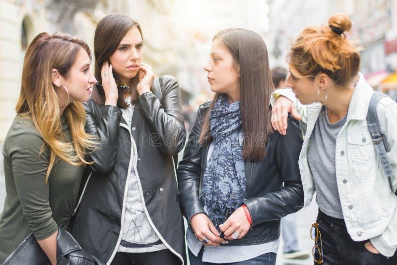 Πορτρέτο τεσσάρων όμορφων φίλων κοριτσιών, κουτσομπολιό στην οδό στοκ φωτογραφία