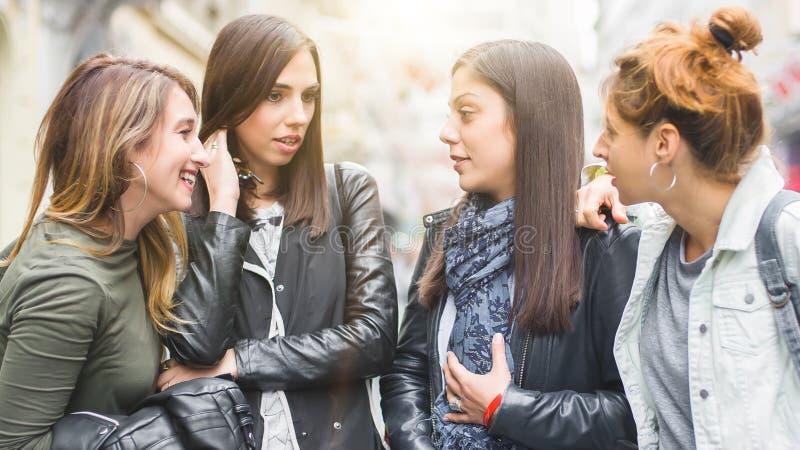 Πορτρέτο τεσσάρων όμορφων φίλων κοριτσιών, κουτσομπολιό στην οδό στοκ φωτογραφίες
