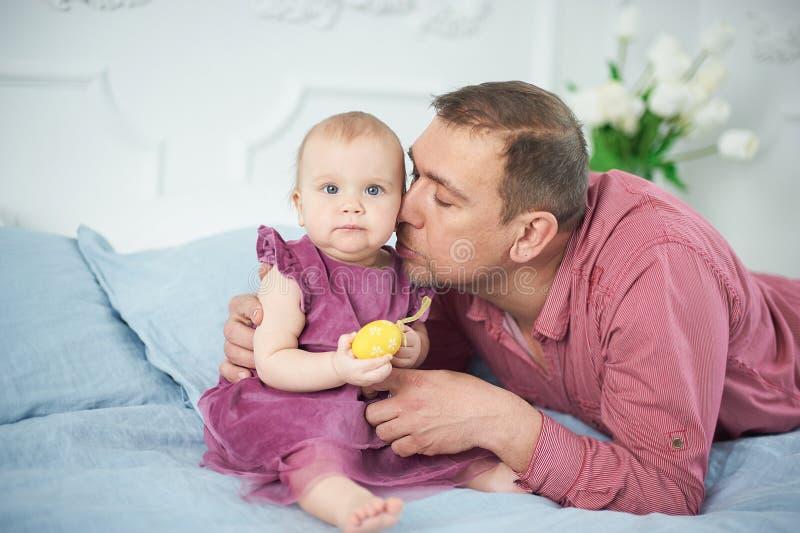 Πορτρέτο της αγάπης του παιχνιδιού πατέρων με 10 μηνών μωρών του στην κρεβατοκάμαρα father' ημέρα του s Πατέρας και κόρη στοκ φωτογραφία με δικαίωμα ελεύθερης χρήσης
