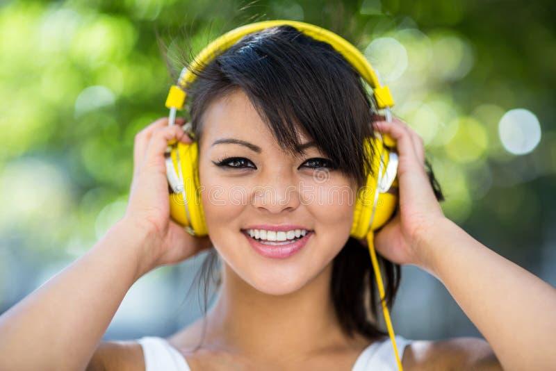 Πορτρέτο της αθλητικής γυναίκας που φορά τα κίτρινα ακουστικά και που απολαμβάνει τη μουσική στοκ φωτογραφίες με δικαίωμα ελεύθερης χρήσης