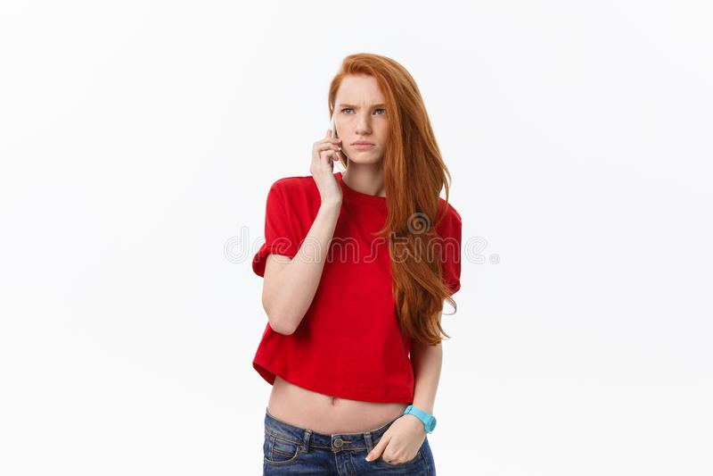 Πορτρέτο της αισιόδοξης γυναίκας στα περιστασιακά ενδύματα που μιλούν στο κινητό τηλέφωνο στεμένος που απομονώνεται πέρα από το ά στοκ φωτογραφία