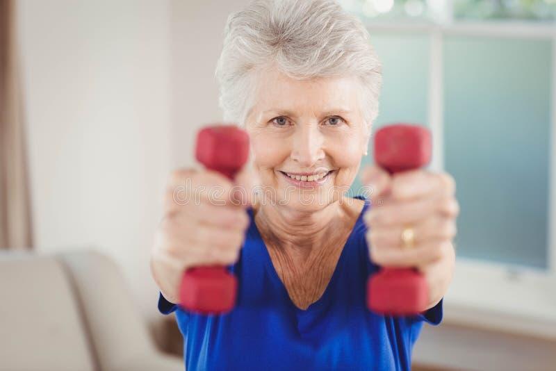 Πορτρέτο της ανώτερης άσκησης γυναικών με τους αλτήρες στοκ φωτογραφία με δικαίωμα ελεύθερης χρήσης