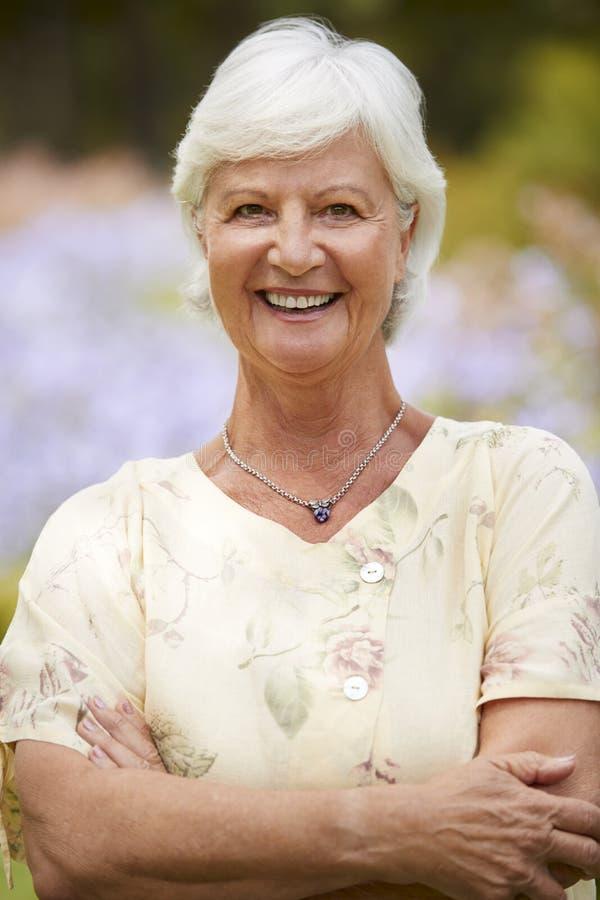 Πορτρέτο της ανώτερης γυναίκας που απολαμβάνεται τον περίπατο από τα κρεβάτια λουλουδιών στο πάρκο στοκ εικόνες με δικαίωμα ελεύθερης χρήσης