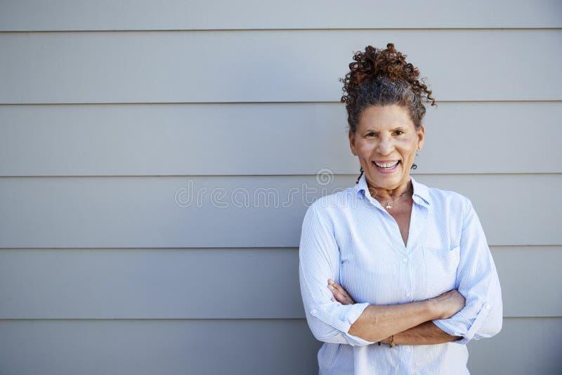 Πορτρέτο της ανώτερης γυναίκας που στέκεται έξω από το γκρίζο Clapboard σπίτι στοκ εικόνες
