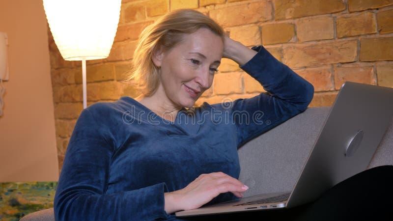 Πορτρέτο της ανώτερης καυκάσιας γυναικείας συνεδρίασης στον καναπέ και της εργασίας με το lap-top πρόθυμα στην άνετη εγχώρια ατμό στοκ εικόνες