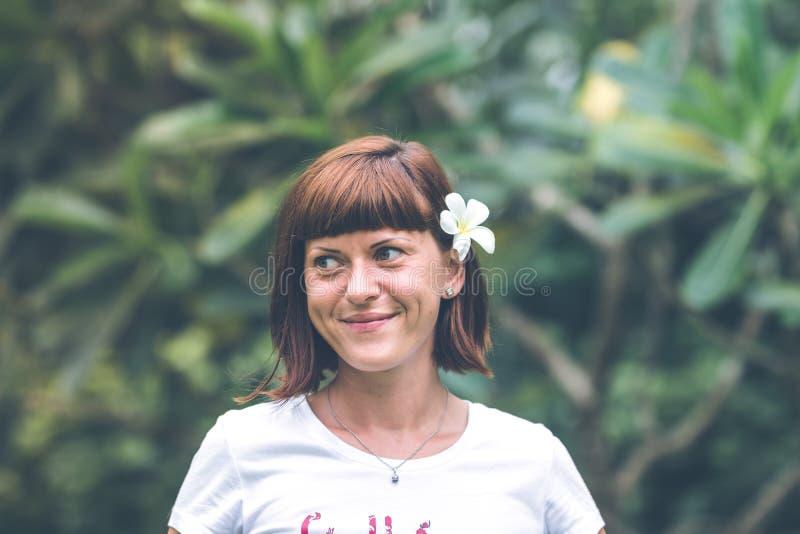 Πορτρέτο της αρκετά νέας γυναίκας με το plumeria frangipani στο αυτί στο όμορφο πράσινο υπόβαθρο Νησί του Μπαλί στοκ φωτογραφία