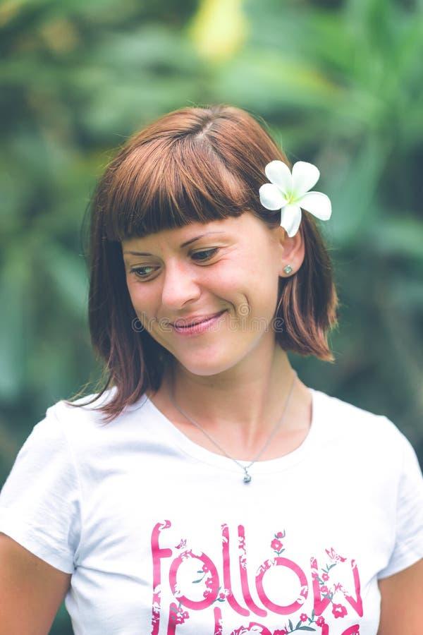 Πορτρέτο της αρκετά νέας γυναίκας με το plumeria frangipani στο αυτί στο όμορφο πράσινο υπόβαθρο Νησί του Μπαλί στοκ εικόνα με δικαίωμα ελεύθερης χρήσης