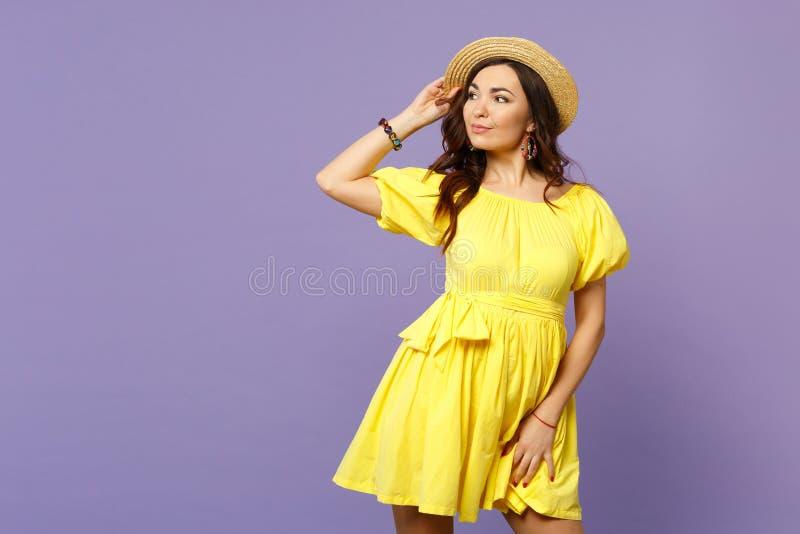 Πορτρέτο της αρκετά νέας γυναίκας στο κίτρινο φόρεμα που κρατά το χέρι στο θερινό καπέλο που κοιτάζει κατά μέρος στη βιολέτα κρητ στοκ φωτογραφία με δικαίωμα ελεύθερης χρήσης