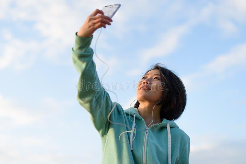Πορτρέτο της αρκετά χαριτωμένης ιαπωνικής γυναίκας με τη σύντομη λήψη τρίχας selfie υπαίθρια χρησιμοποιώντας το τηλέφωνό της Μπλε στοκ φωτογραφία