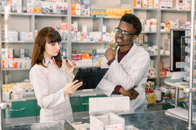 Πορτρέτο της αρσενικής αφρικανικής στάσης φαρμακοποιών με τη γυναίκα συνάδελφος με την περιοχή αποκομμάτων, σύγχρονο υπόβαθρο φαρ στοκ εικόνα