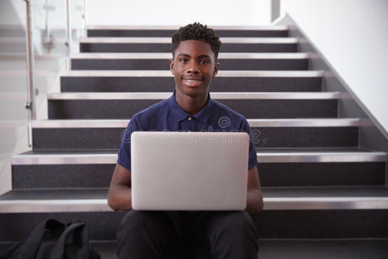Πορτρέτο της αρσενικής συνεδρίασης σπουδαστών γυμνασίου στη σκάλα και της χρησιμοποίησης του lap-top στοκ εικόνες