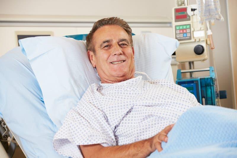 Πορτρέτο της αρσενικής υπομονετικής χαλάρωσης στο νοσοκομειακό κρεβάτι στοκ φωτογραφία