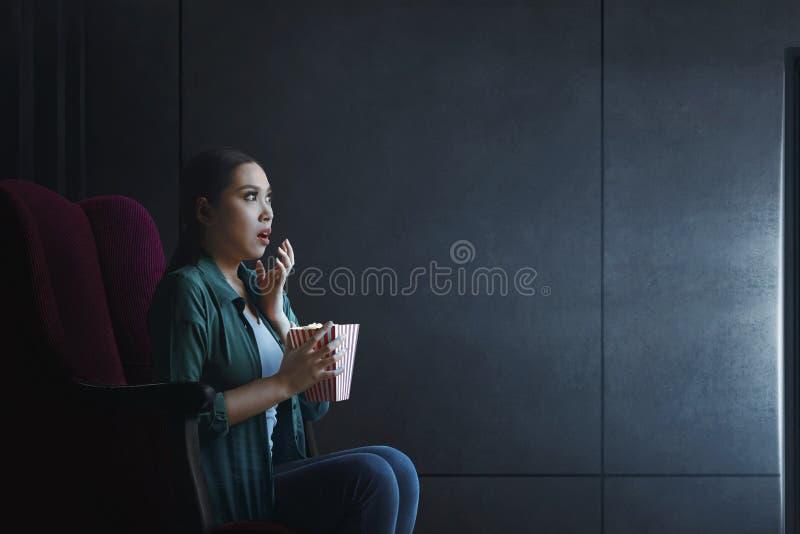 Πορτρέτο της ασιατικής γυναίκας με popcorn τη ταινία τρόμου προσοχής στοκ εικόνες