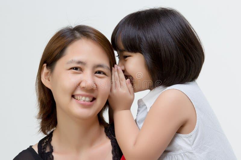 Πορτρέτο της ασιατικής μητέρας που ψιθυρίζει στην κόρη της στοκ φωτογραφίες