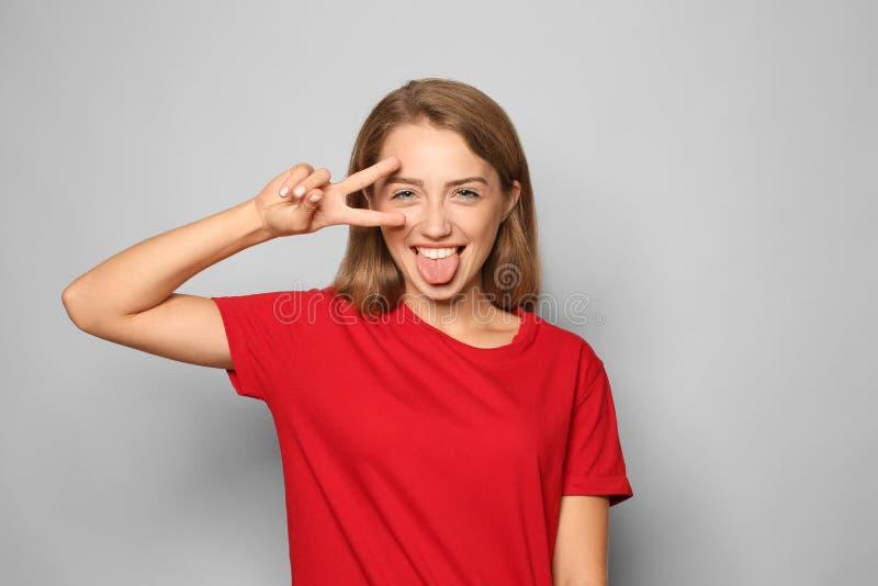 Πορτρέτο της αστείας νέας γυναίκας που παρουσιάζει χειρονομία νίκης στο ελαφρύ υπόβαθρο στοκ φωτογραφία με δικαίωμα ελεύθερης χρήσης