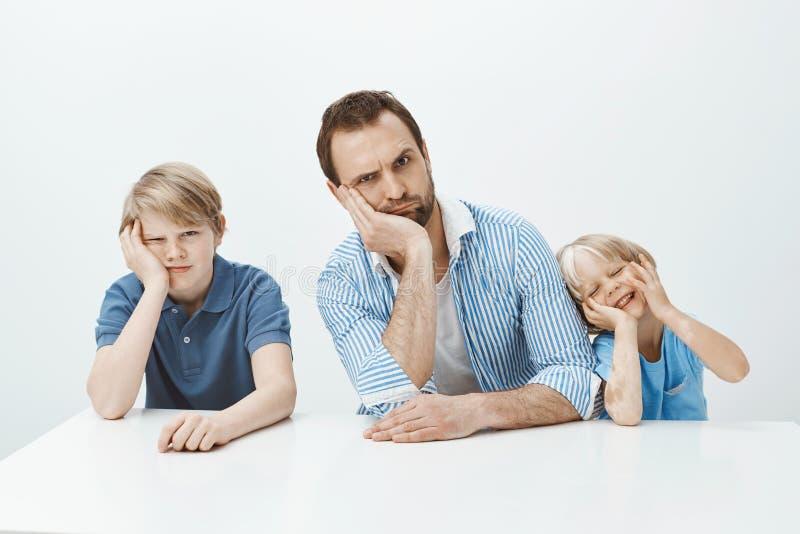 Πορτρέτο της αστείας οικογένειας του πατέρα και των γιων που κάθονται στον πίνακα, κλίνοντας κεφάλι σε διαθεσιμότητα και που κάνο στοκ εικόνα