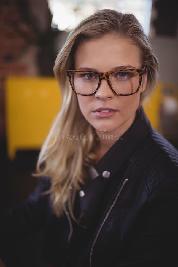 Πορτρέτο της βέβαιας νέας ελκυστικής γυναίκας που φορά eyeglasses στοκ εικόνα με δικαίωμα ελεύθερης χρήσης
