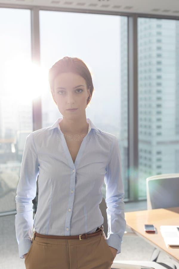 Πορτρέτο της βέβαιας νέας επιχειρηματία που στέκεται στην αίθουσα συνεδριάσεων στο γραφείο στοκ φωτογραφία