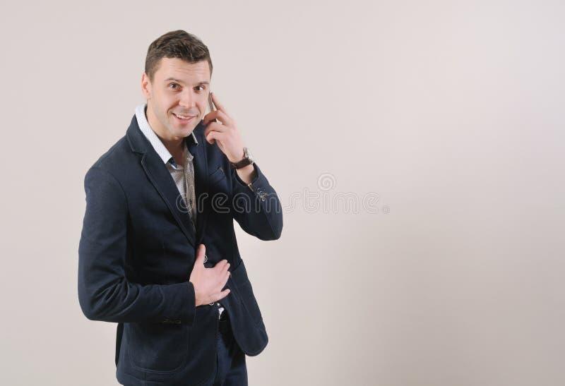 Πορτρέτο της βέβαιας ομιλίας επιχειρηματιών χαμόγελου στο τηλέφωνο στοκ εικόνες