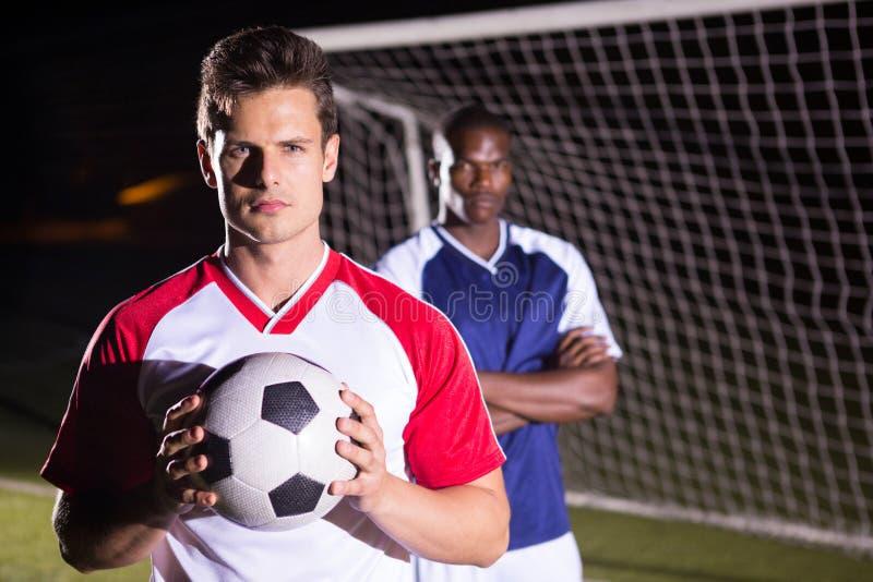 Πορτρέτο της βέβαιας σφαίρας εκμετάλλευσης ποδοσφαιριστών με τον αντίπαλο αθλητή στοκ φωτογραφίες