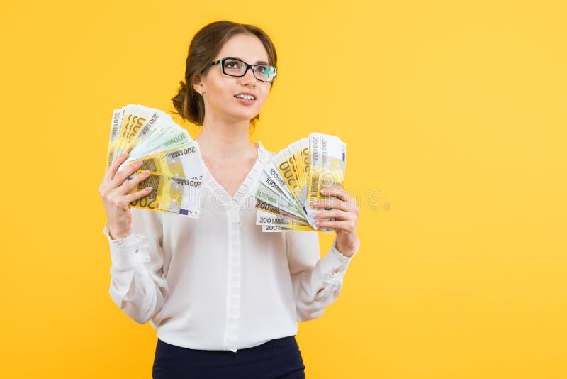 Πορτρέτο της βέβαιας όμορφης ευτυχούς νέας επιχειρησιακής γυναίκας με τα χρήματα στα χέρια της που στέκονται στο κίτρινο υπόβαθρο στοκ εικόνα με δικαίωμα ελεύθερης χρήσης