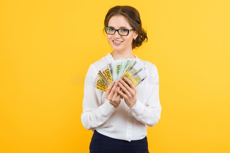 Πορτρέτο της βέβαιας όμορφης ευτυχούς νέας επιχειρησιακής γυναίκας με τα χρήματα στα χέρια της που στέκονται στο κίτρινο υπόβαθρο στοκ εικόνες