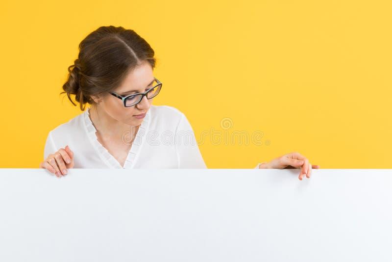 Πορτρέτο της βέβαιας όμορφης ευτυχούς χαμογελώντας νέας επιχειρησιακής γυναίκας που παρουσιάζει κενό πίνακα διαφημίσεων στο κίτρι στοκ φωτογραφίες