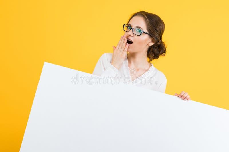 Πορτρέτο της βέβαιας όμορφης ευτυχούς χαμογελώντας νέας επιχειρησιακής γυναίκας που παρουσιάζει κενό πίνακα διαφημίσεων στο κίτρι στοκ εικόνες