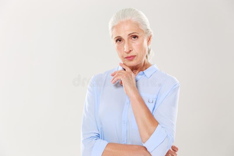 Πορτρέτο της γοητείας της σοβαρής ηλικιωμένης κυρίας, στο μπλε πουκάμισο, σχετικά με το χ στοκ φωτογραφία με δικαίωμα ελεύθερης χρήσης