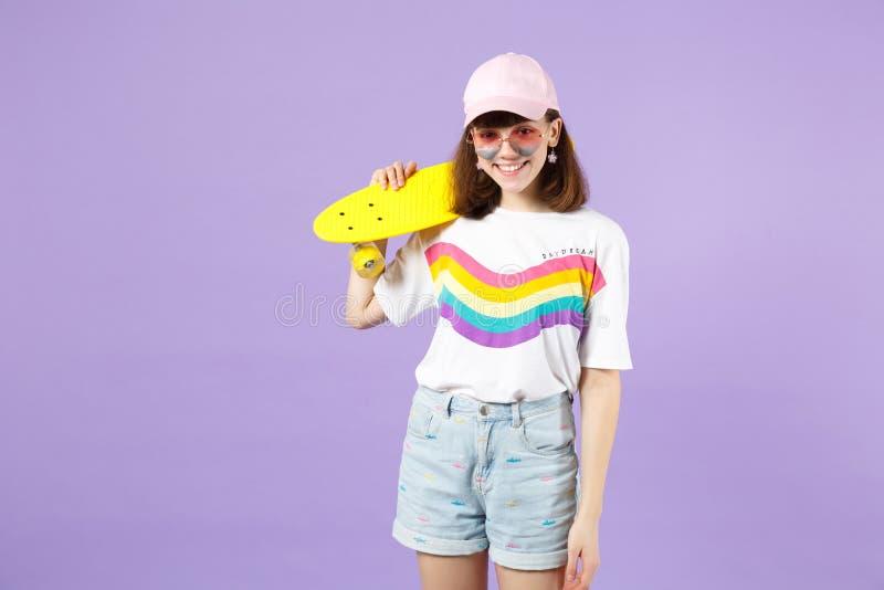 Πορτρέτο της γοητείας του κοριτσιού εφήβων στα ζωηρά ενδύματα, eyeglasses καρδιών που κρατά κίτρινο skateboard απομονωμένο στην ι στοκ φωτογραφία με δικαίωμα ελεύθερης χρήσης