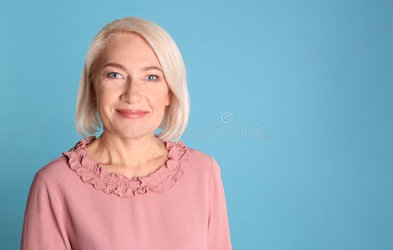 Πορτρέτο της γοητείας της ώριμης γυναίκας με το υγιές όμορφο δέρμα προσώπου και του φυσικού makeup στο μπλε υπόβαθρο στοκ εικόνα με δικαίωμα ελεύθερης χρήσης