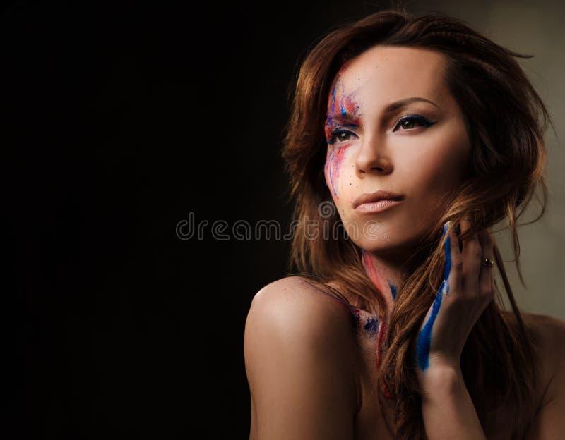 Πορτρέτο της γυναίκας με δημιουργικό που χρωματίζεται makeup σε ένα σκοτεινό υπόβαθρο στοκ φωτογραφία με δικαίωμα ελεύθερης χρήσης