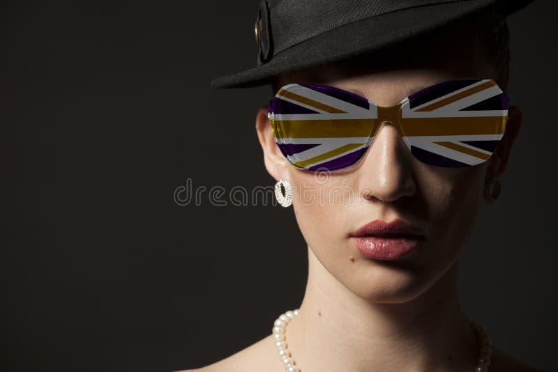 Πορτρέτο της γυναίκας με τα βρετανικά γυαλιά ηλίου σημαιών στοκ εικόνα