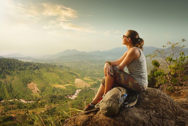 Πορτρέτο της γυναίκας με τη συνεδρίαση backpacker πάνω από το βουνό στοκ εικόνα με δικαίωμα ελεύθερης χρήσης