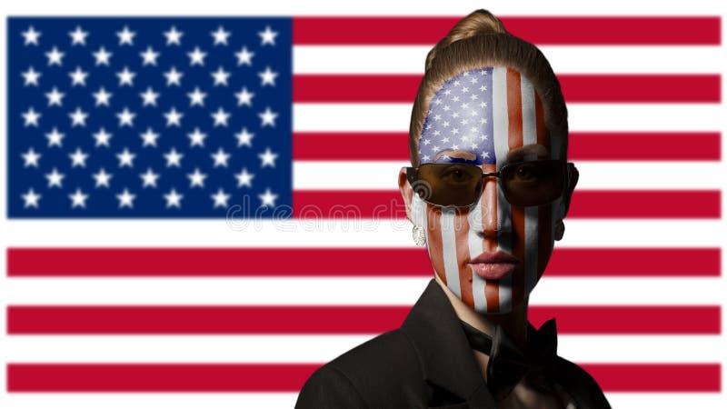 Πορτρέτο της γυναίκας με τη χρωματισμένη ΑΜΕΡΙΚΑΝΙΚΑ σημαία και τα γυαλιά ηλίου στοκ φωτογραφία με δικαίωμα ελεύθερης χρήσης