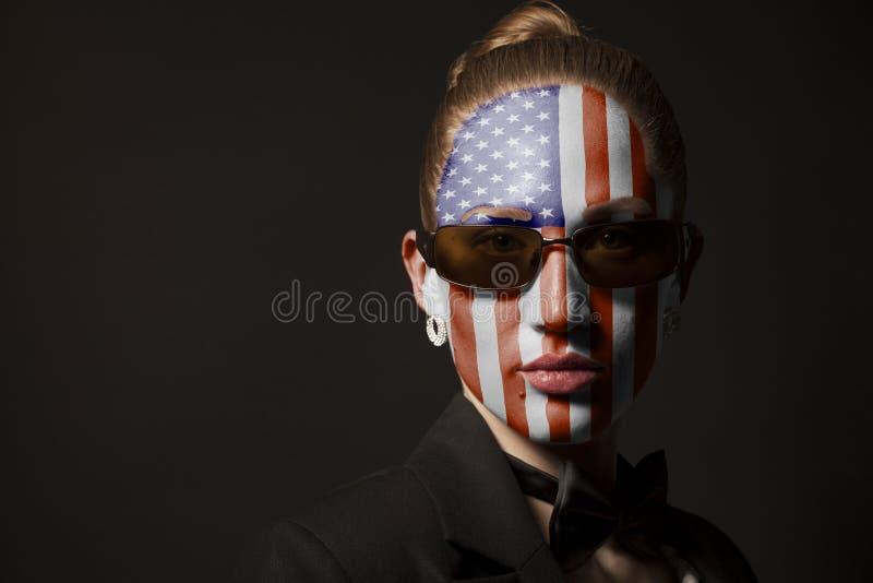 Πορτρέτο της γυναίκας με τη χρωματισμένη ΑΜΕΡΙΚΑΝΙΚΑ σημαία και τα γυαλιά ηλίου στοκ φωτογραφία