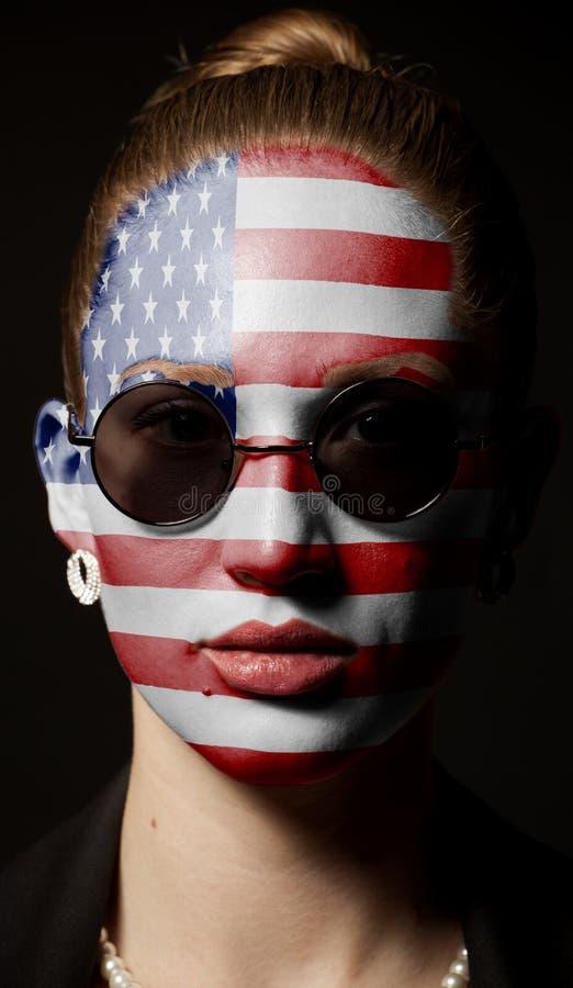 Πορτρέτο της γυναίκας με τη χρωματισμένη ΑΜΕΡΙΚΑΝΙΚΗ σημαία με τα γυαλιά ηλίου στοκ εικόνα με δικαίωμα ελεύθερης χρήσης