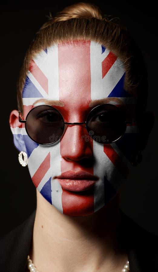 Πορτρέτο της γυναίκας με τη χρωματισμένη βρετανική σημαία του Union Jack με τα γυαλιά ηλίου στοκ φωτογραφία με δικαίωμα ελεύθερης χρήσης
