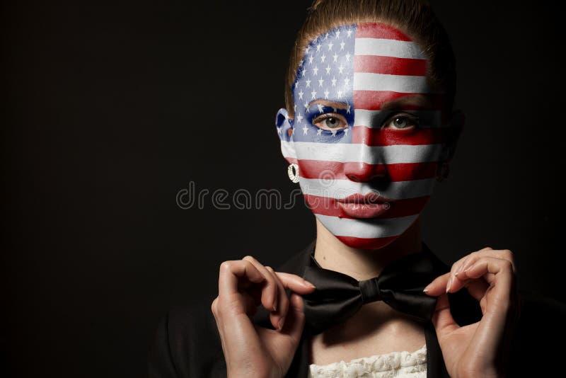 Πορτρέτο της γυναίκας με τη χρωματισμένους ΑΜΕΡΙΚΑΝΙΚΗ σημαία και το δεσμό τόξων στοκ εικόνες