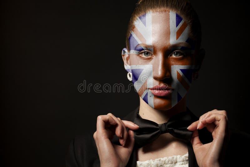 Πορτρέτο της γυναίκας με τη χρωματισμένους βρετανικούς σημαία του Union Jack και το δεσμό τόξων στοκ φωτογραφία με δικαίωμα ελεύθερης χρήσης